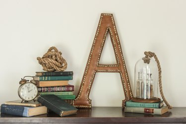 """A large leather """"A"""" with nailhead trim, staged with stacked vintage books, glass cloche, and vintage clock."""