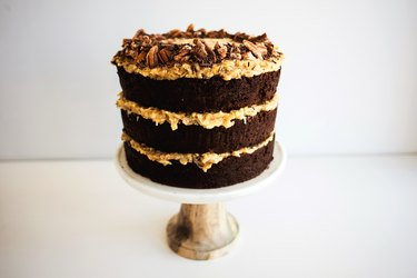 German chocolate cake layers assembled on a cake stand.