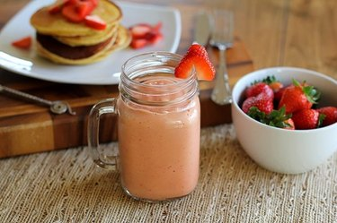 A healthy strawberry smoothie served with fresh strawberries and pancakes.