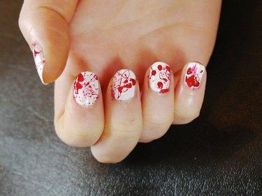 Red blood splatter polish on white nails.