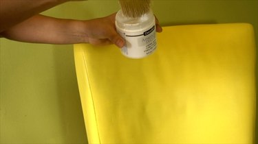 Applying cream wax to fabric upholstery painted with chalk paint.