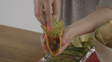 Filling taco with meat, cheese and lettuce.