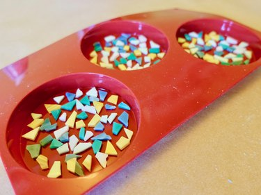Arranging glass tile pieces on the bottom of silicone mold for DIY modern terrazzo coasters