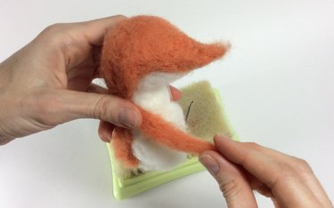 Female hands holding an orange and white fox with one arm.