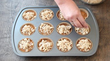 Topping muffin batter with streusel.