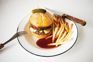 Beef hamburger a brioche bun on a plate with French fries and ketchup.