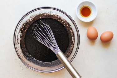 Bowl and whisk with butter, sugar, and cocoa powder mixed together
