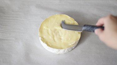 pressing knife into brie that's too firm