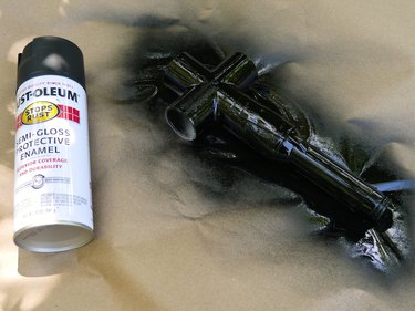 A can of black spray paint and the painted handle unit.