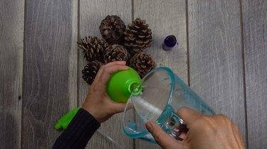 Making cinnamon oil solution for DIY cinnamon-scented pinecones.