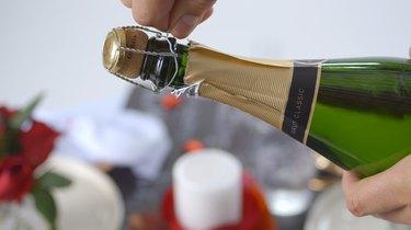 Remove wire hood over cork.