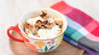 finished carrot mug cake topped with frosting and walnuts