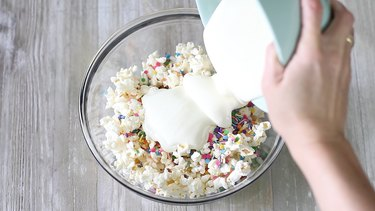 pouring melted white chocolate over popcorn and sprinkles