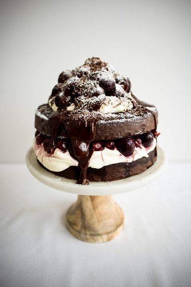 A Black Forest Cake on a cake stand, ready to serve.