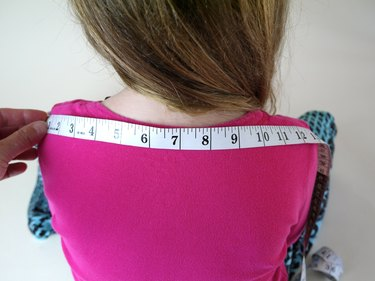 The back of a 6 year old girl with a measuring tape.