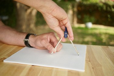 A compass is shown drawing a circle on foam core
