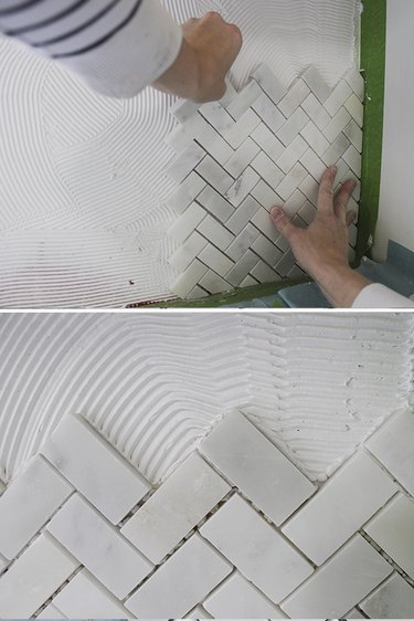 Pushing tile into mastic.
