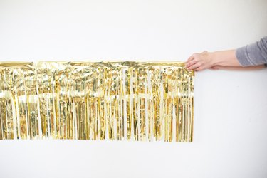 Hands hanging gold fringe garland on white wall