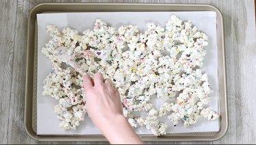 spreading rainbow popcorn on baking tray