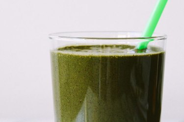 A delightfully rich, green smoothie with a green straw.