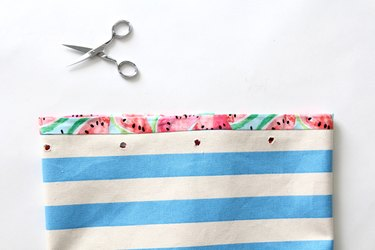 cut holes in fabric prior to setting grommets
