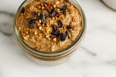 A small mason jar filled with chocolate protein overnight oats.