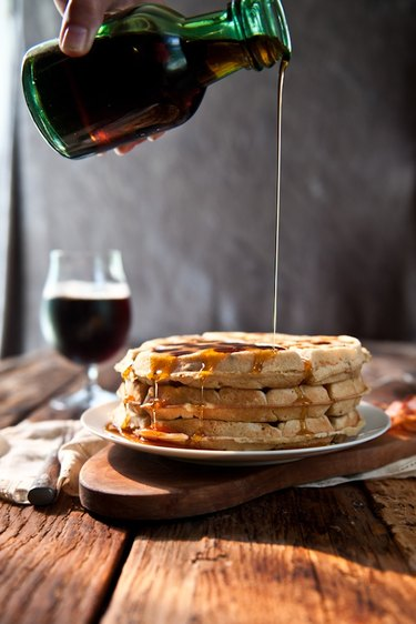 Maple syrup  being poured over a stack of waffles.