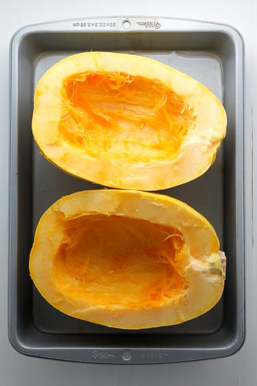 Roasting pan with two halves of a spaghetti squash.
