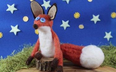 Needle felted fox on a wood log