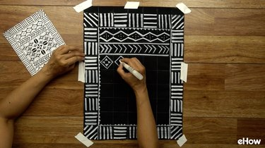 Drawing with paint pen to create DIY mudcloth-inspired wall hanging.