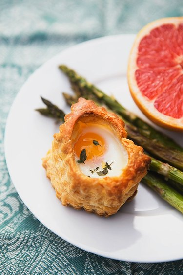 Plate of the pastry baked egg, asparagus and half of a grapefruit.