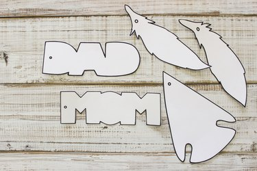 """Printed and cut out air freshener designs: capital, block letters spelling """"DAD"""" and """"MOM"""", an arrowhead, and 2 feathers."""