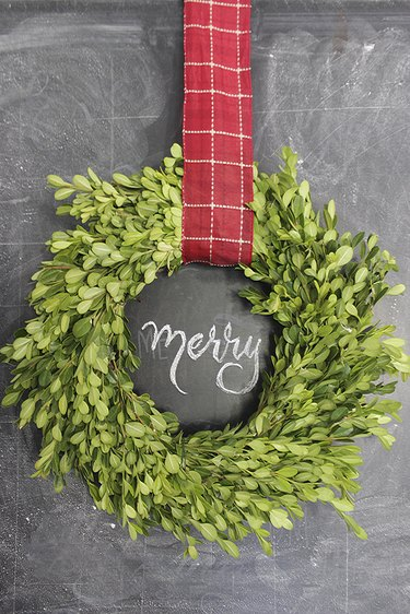 Boxwood wreath hung with red checked ribbon for Christmas