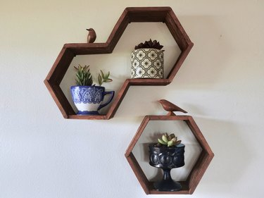 DIY hexagon, honeycomb shelves made using popsicle sticks, hot glue, and wood stain.