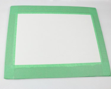 Secure paper to board with tape.