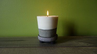 Lit DIY candle with cement base on table.
