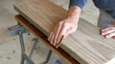 Sanding rough edges along the wood