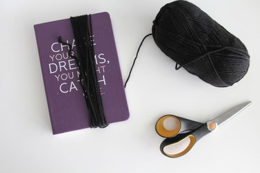 Wrap black yarn around a book