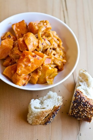 A bright orange bowl of spicy stewed butternut squash served with bread.