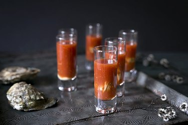 Six bloody mary oyster shooters on a metal tray