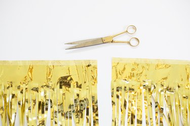Cut gold fringe with gold scissors