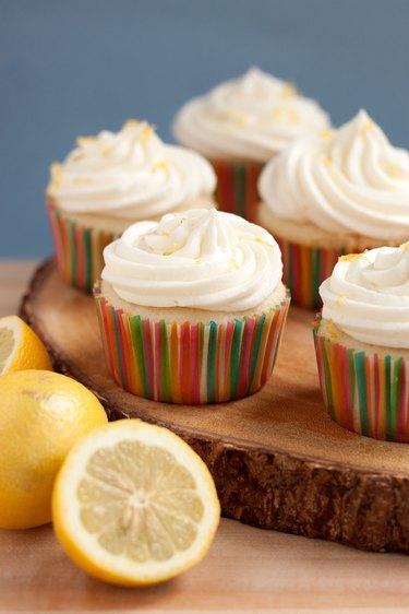Close up of lemonade cupcake with sliced lemons.