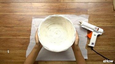 Gluing rope onto basket for DIY desert-style baskets.