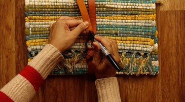 Assembling upcycled no-sew clutch from a placemat and belt