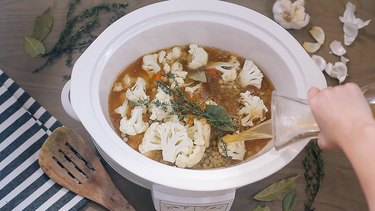 Pouring broth into crockpot
