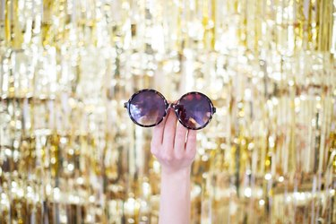 Hand holding sunglasses in front of gold backdrop