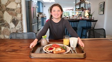 young girl serving breakfast tray featuring toad-in-the-hole
