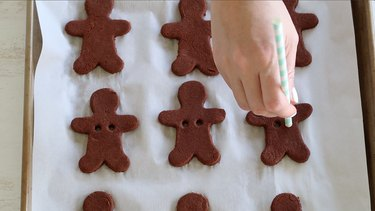 Cutting holes in gingerbread men for ribbon