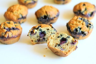 Blueberry muffins, with one cut open to show texture.
