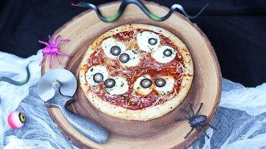 Eyeball pizza served on wood platter